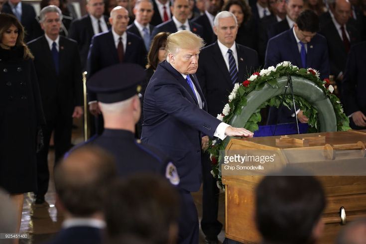 U.S. President Donald Trump touches the casket of Christian evangelist and Southern Baptist minister Billy Graham as he lies in honor in the U.S. Capitol Rotunda February 28, 2018 in Washington, DC. A spiritual counselor for every president from Harry Truman to Barack Obama and other world leaders for more than 60 years, Graham died February 21 at the age of 99.