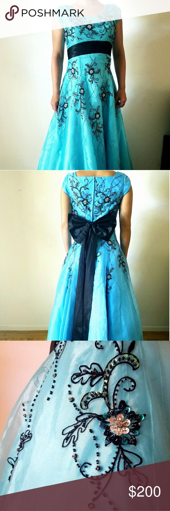 Modest A-line Blue Prom Dress with Black Beading Floor-length, A-line, cap sleeve prom dress purchased to attend a Mormon prom. Modestly styled in the front and back.  Dress is blue with a sheer layer on top and white-netting petticoat underneath. Black bow snaps on to the black waist band in back.  Minor damage to under-layers (caught on heel of shoe) and some beading on bodice. Needs to be ironed, but otherwise in good condition.  Worn once to Mormon prom and once to a high school prom…