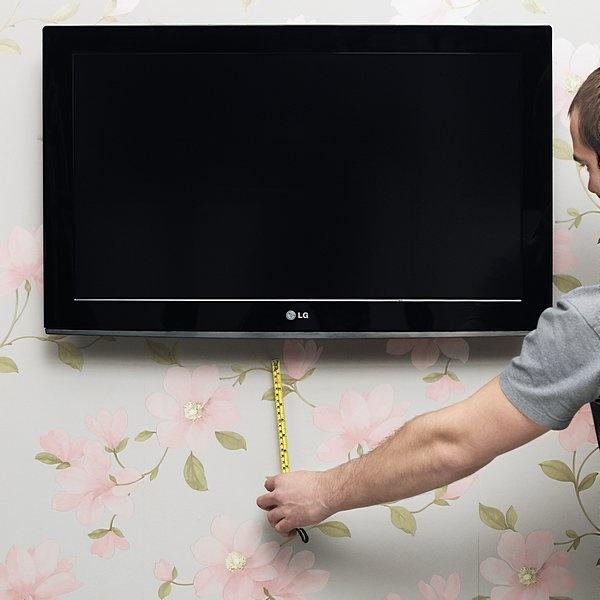 Punto 1  Misurare il lettore di DVD e il set top box per stabilire le dimensioni dell'armadietto. Segnare sul muro la posizione, centrata ad esempio, lasciando uno spazio per accedere ai comandi sotto il televisore a schermo piatto e per i cavi. Misurare la spazio tra il bordo inferiore del televisore a schermo piatto, dove i cavi devono essere nascosti dalla canalina bianca, e il bordo superiore dell'armadietto.