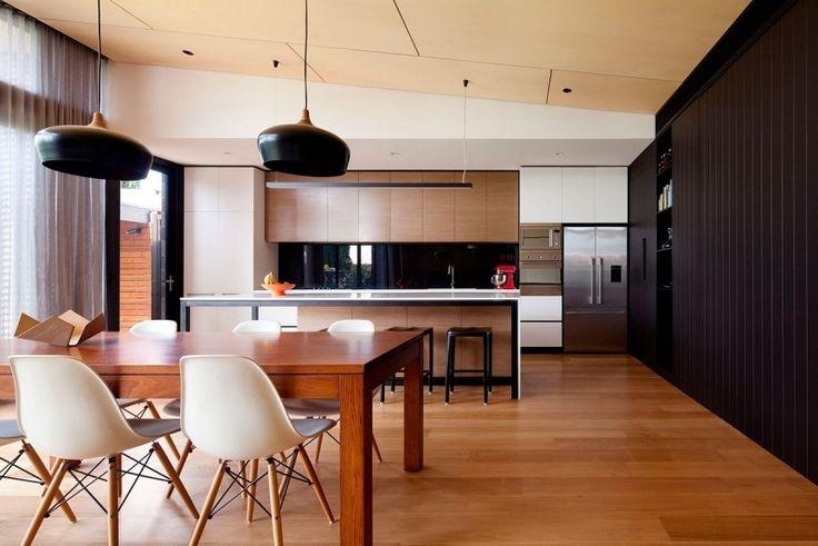 cuisine avec coin repas élégant, suspensions noires, armoires en bois clair et frigo et fours encastrables