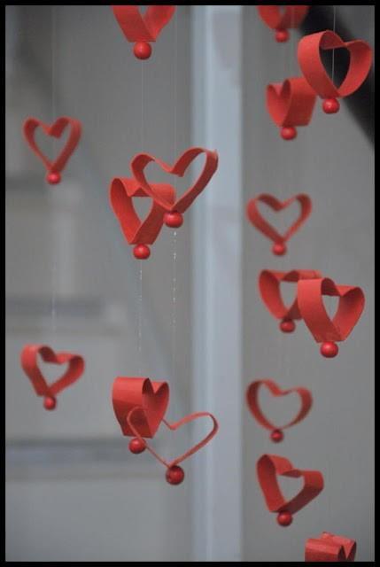 """Faça um lindo móbile de coração reciclando rolinhos de papel higiênico. Pinte o rolinho de vermelho, corte em """"fatias"""", modele como um coração e prenda com fios de nylon e miçangas."""