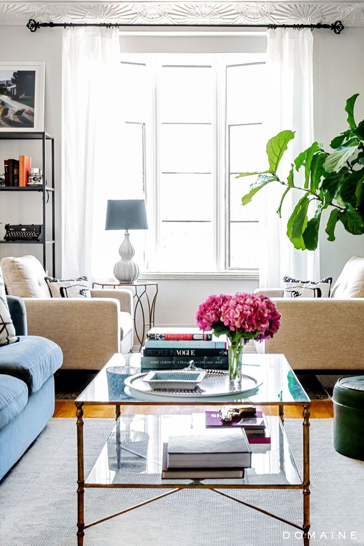 Styled coffee table with flowers and coffee table books, indoor plant, natural light
