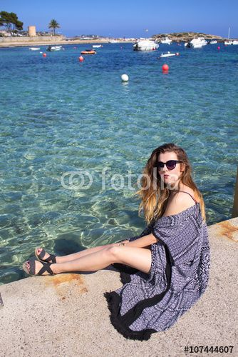 Attractive young woman sitting by the sea over the clear water