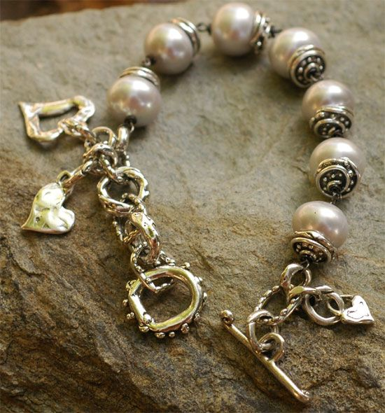 """Icing on the Cake Luscious 13mm freshwater pearls with just a bit a lavender shimmer. Capped with swirls of sterling silver. Sterling silver links laced with a few of our happy hearts.  Bracelet size is 7.5"""" NOTE: When sizing a chunkier style, the gems take up some of the circumference.  An Original Artisan bracelet by Cathy Dailey"""