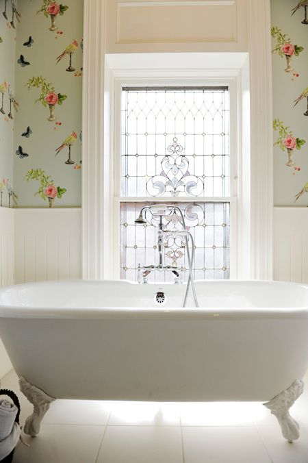Bathroom with beautiful windows, a classic clawfoot bath and aqua wallpaper. Love the wallpaper.