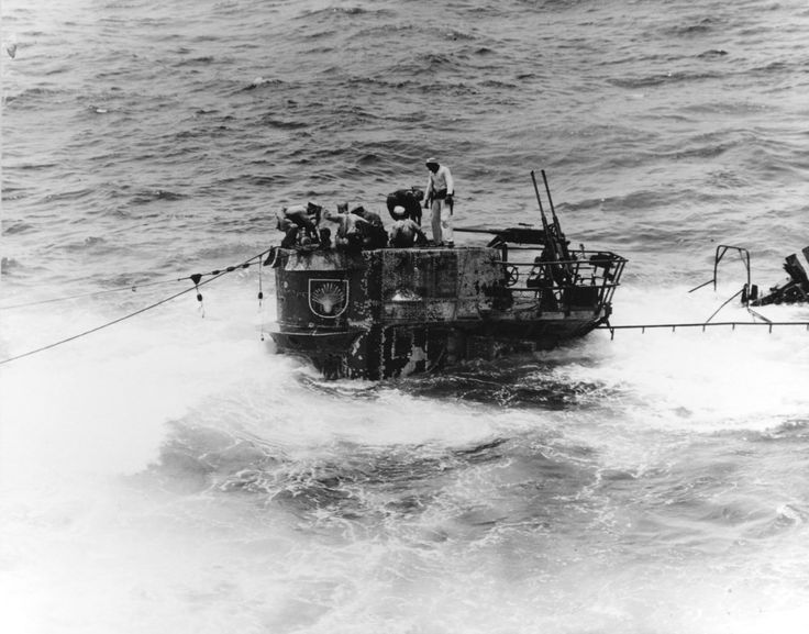 A salvage party from USS Guadalcanal on the captured German submarine U-505, 4 Jun 1944 in the eastern Atlantic. Note the twin 20mm anti-aircraft guns and the seashell insignia on the tower.