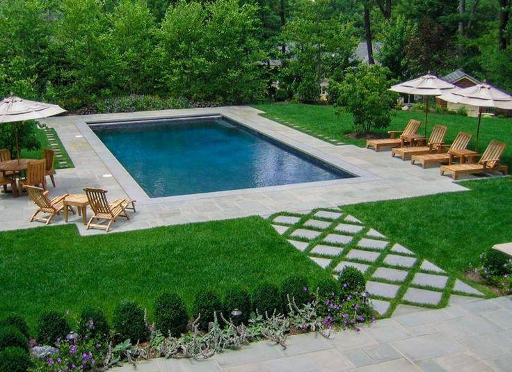 aménagement jardin paysager autour de la piscine avec plage en dalles et chaise longues en bois