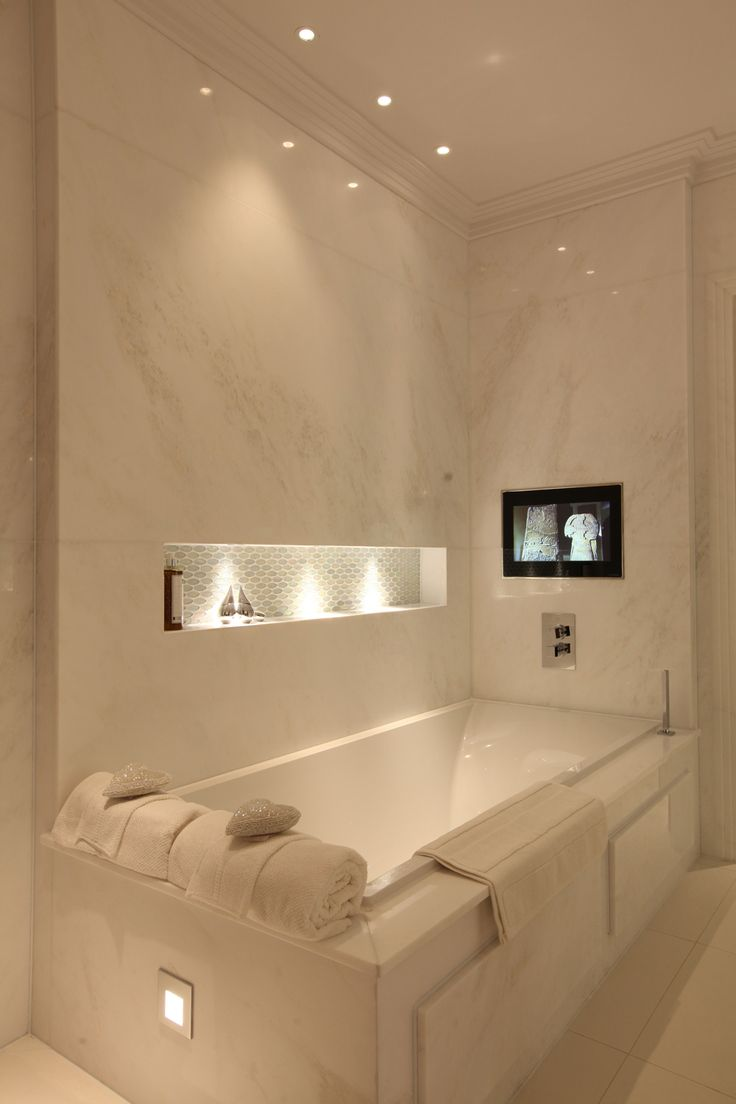THIS is ideal- ceiling spotlights, in built shelves next to the bath and a tv built into the wall behind a glass screen to keep it from getting damaged by steam/water