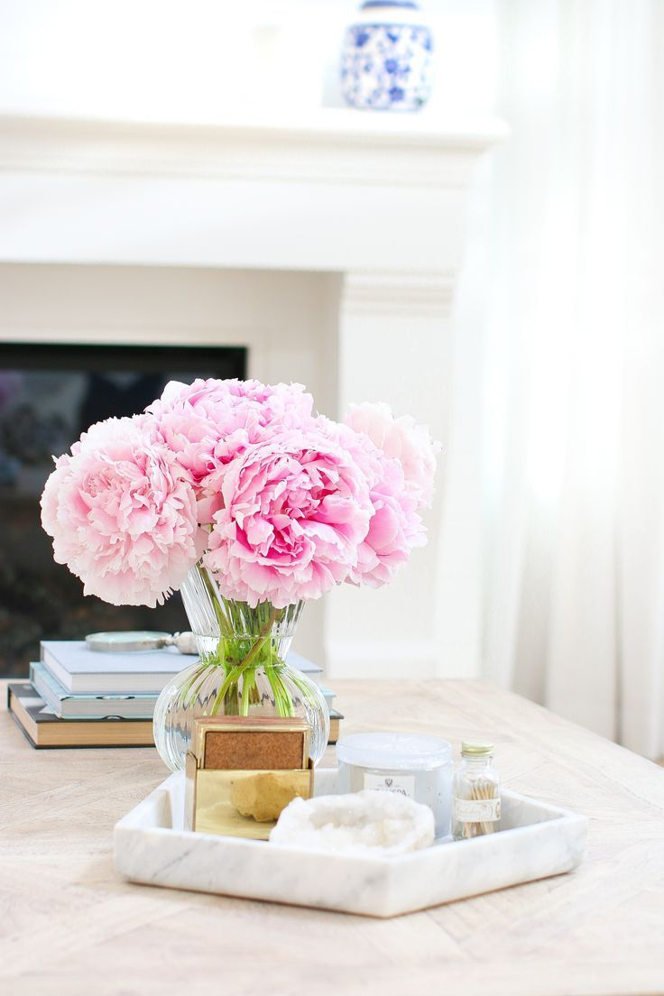 The right coffee table styling can pull the look of a room together. Corral small items onto a marble tray and add some colorful blooms for a simple, and elegant look.
