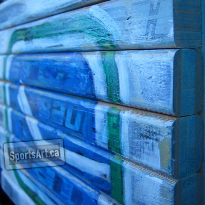 """Artist Jeremie White grew up with the iconic Canucks """"Rink and Stick"""" logo tattooed on his heart. In this piece he has painted the west coast blue and green over a canvas of hockey sticks!"""