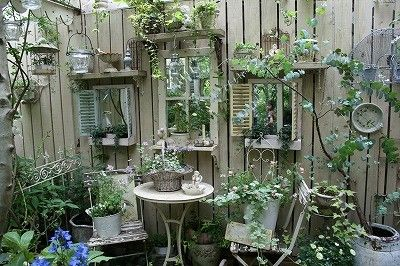 """Windows"" in the fence.  Great use of shutters, shelves and mirrors to suspend disbelief in a solid barrier."