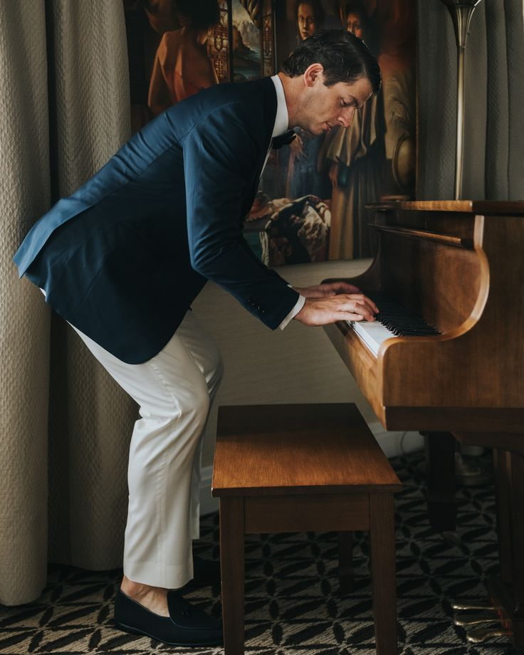 groom playing piano; white pants and blue blazer groom style; PHOTOGRAPHY Joel + Justyna Bedford;
