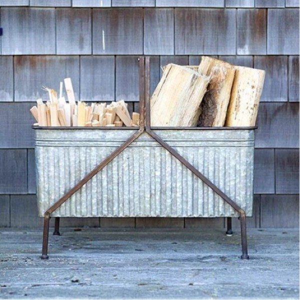 Embossed Metal rustic firewood stand. Adorable for inside with birch log or firewood. This stand is a decorative piece but very functional too. This would be cute beside an outdoor fireplace on a pati