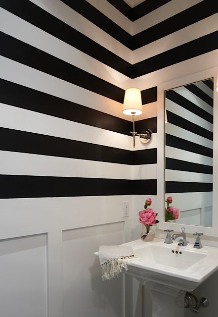 Black and white stripes down half way really creating a stylish and powerful effect in this powder room Lynn Morgan Design