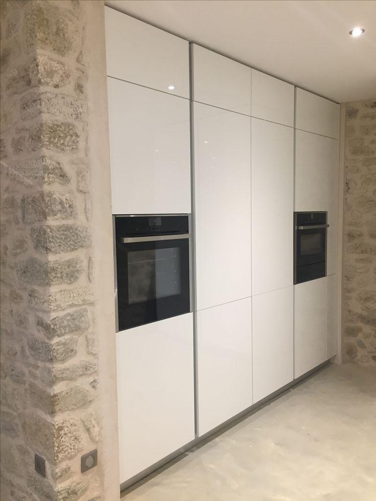 Fours NEFF intégrés dans un mur d'armoires qui comprend aussi un réfrigérateur DeDietrich et un combiné réfrigérateur/congélateur LIEBHERR avec ice maker (portes au centre).