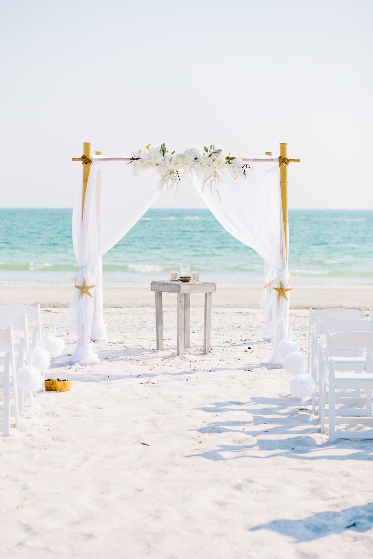 Elegant white beach wedding arbor.