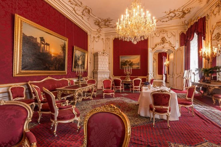 luxury crystal chandelier design hanging in white gold ceiling restaurant also red gold dining chair as well red floral wallpaper and rug covering floor including classic frame on the wall