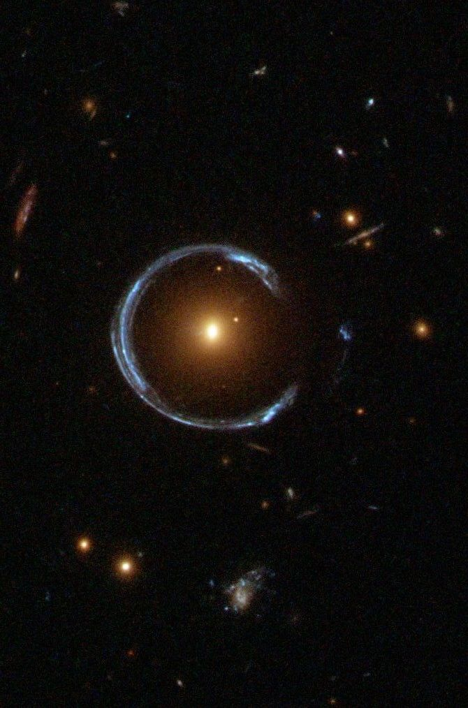 """An """"Einstein Ring""""or gravitational lensing at work: the blue galaxy is behind the yellow galaxy but we can see it because the light from the far galaxy gets wrapped around by the closer galaxy. Photo NASA/Hubble"""