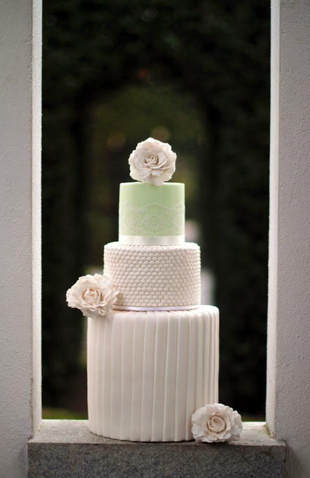 Double barrel pleated bottom tier. Pearl effect second tier and pretty lace on green fondant top tier. Wedding cake with white gumpaste flowers. Design by Oh Gateaux.  Photography by Simon Fitzpatrick. https://www.facebook.com/ohgateaux