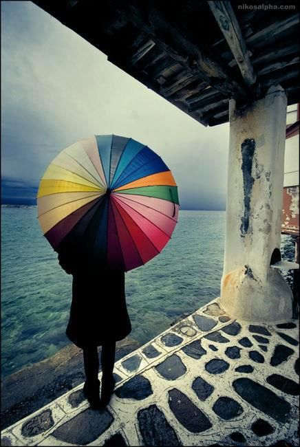 colourful umbrella on a dark ocean landscape, in an old shelter