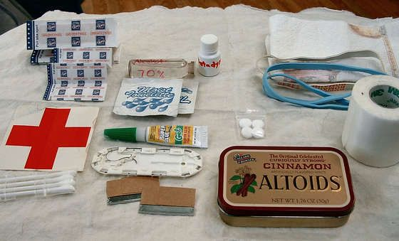 Altoids First Aid Tin idea...Bands Aids, moist Towelettes (optional), Rubber Bands, Tape,  Aspirin,  Swabs, Paper Towel (or gauze), Razor Blades  Super Glue, Betadine, Isopropyl Alcohol, (this one had a suture kit which I would eliminate). I would add antibiotic ointment w/pain reliever, a needle (for splinters/stingers), tweezers, and some benedryl tabs.