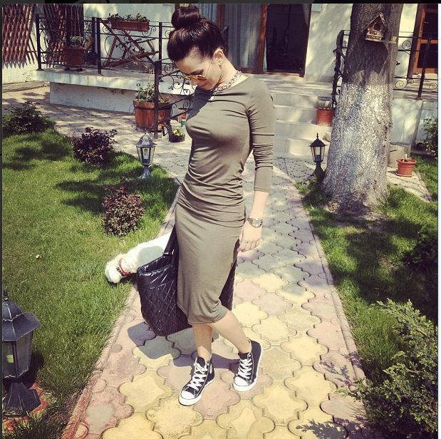 Sweater dress and converse sneakers.inna is wearing it well
