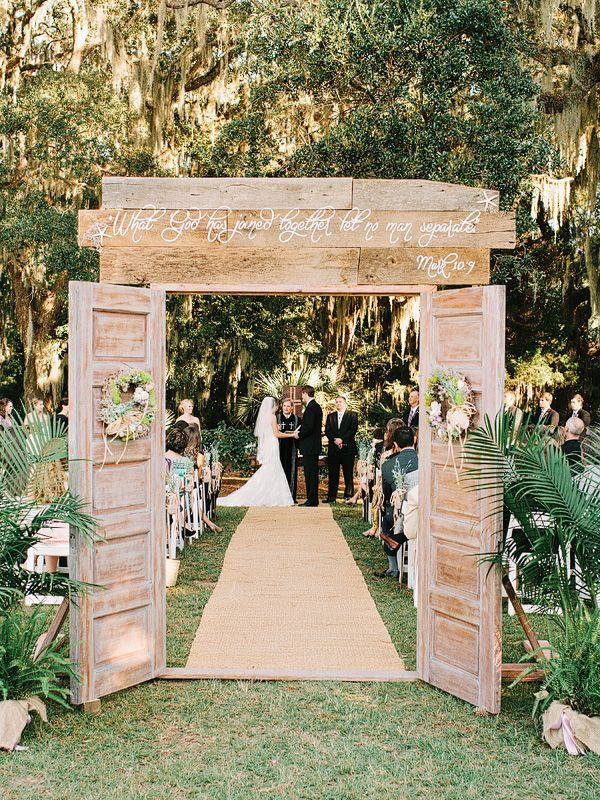 "This couple created an ""outdoor church"" for their ceremony with rustic doors and a biblical quote above the entrance."