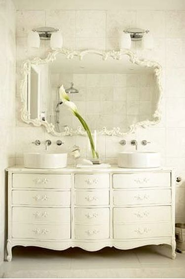 This is a beautiful display of Traditional design- vitreous china vessel sinks supplied by wall mount lavatory faucets upon an antique bathroom cabinet.