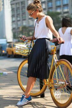 weißes Trägershirt, schwarzer Falten Midirock, weiße und blaue niedrige Sneakers, schwarze Leder Umhängetasch