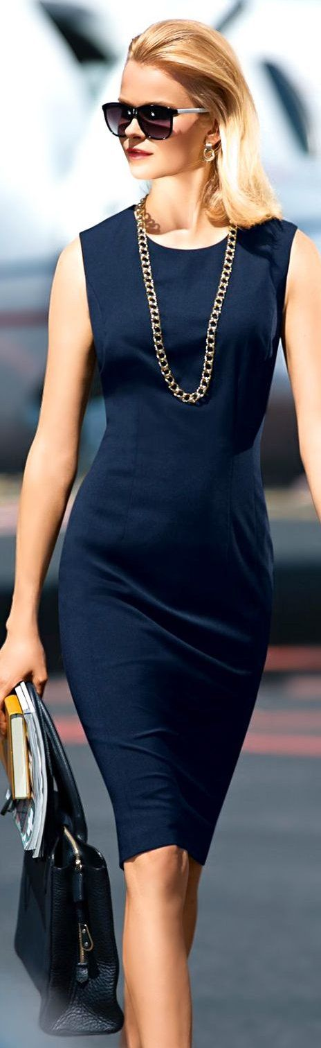 Beautiful body-hugging navy sheath. Sleeveless and knee length with round neckline. Long chunky chain necklace, earrings, oversized sunnies and black soft briefcase-style tote. Timeless. Style Planet |  Madeleine Couture