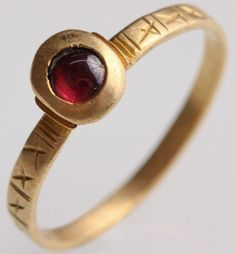 Jewelry Auction - NO RESERVE ITEM - Nov 30th 2016 - Medieval Garnet Ring. THIS LOT IS BEING OFFERED WITH NO RESERVE. Possibly 15th-16th century. The hammered flat gold band on this simple ring is decorated with hatchings and set with an ellipsoid bezel holding a cabochon garnet. Small rectangular gold pieces define the shoulders of the ring, where bezel meets hoop. This and more important ancient art for sale on CuratorsEye.com