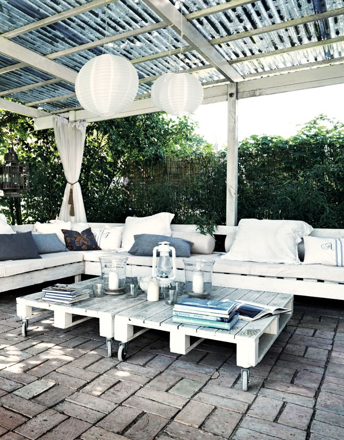 More pallet patio, gardening, DIY furniture ideas at http://pinterest.com/wineinajug/passion-for-pallets/ Inspiration for the conservatory. Make your own outdoor furniture, and create spatial sense with sheer curtains. DIY outdoor furniture is self-made. Lounge Table made from pallets with wheels. Skira curtains creates space, and outdoor lighting gives a beautiful and ambient glow at night.