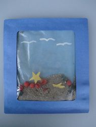 Kids Outdoor Summer Craft-Sandwich zip lock bag, 2 dk. blue pieces of paper, sand, shells and stars.  Seagulls on both ends so that you can turn it upside down too!