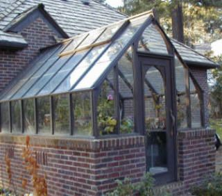 This painted wood Tudor greenhouse is attached to the house at the gable end and has a brick base providing thermal mass