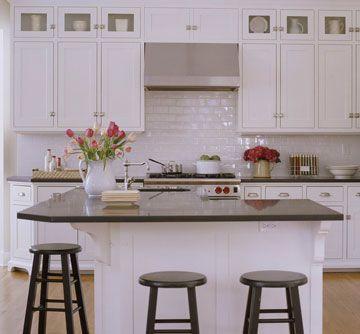 White cabinets, black counters, and white subway tile backsplash