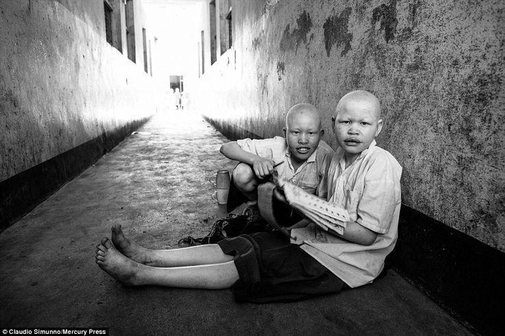 Two teenagers at the orphanage do their homework together while sitting in a hallway in th...