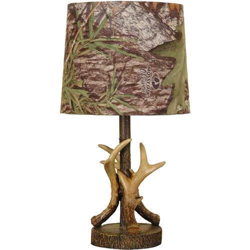 """Mossy Oak lamps and shades like this Deer Antler Accent Mossy Oak Lamp provide a unique set of lighting items that are great for developing an outdoorsy look. This dark woodtone, deer lamp goes great in log homes and hunting cabins. This deer antler lamp has a hand-painted decorative base and features a Mossy Oak Obsession camo pattern fabric tapered drum shade. The dark woodtone, deer lamp has a push-through on/off switch, 60"""" black cord, and takes 1 max type-A 60W bulb or 1 max 15W SBCFL…"""