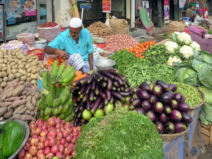 A vegetable vendor waits on the main street of Dhamrai northwest of Dhaka, Bangladesh.