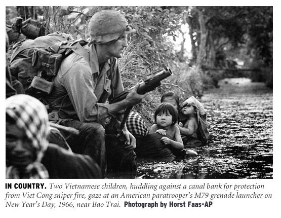 Two Vietnamese children, huddling against a canal bank for protection from Viet Cong sniper fire, gaze at an American paratrooper's M79 grenade launcher on New Year's Day, 1966, near Bao Trai. - (Vietnam pics by Horst Faas)