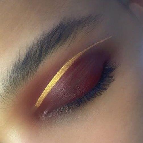 Un maquillage des yeux étonnant : un fard à paupières mat bordeaux avec un trait d'eye liner doré