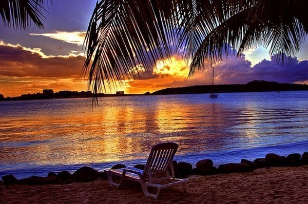 Sunset on the beach with a lounge chair and palm trees