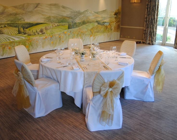 Gold Dark organza sashes on white cotton chair covers at The Vineyard at Stockcross by Simply Bows and Chair Covers