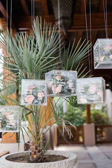 Unique and original idea for a table plan - perspex boxes filled with fresh florals - scripted with white text with table names - Photo from Louise & Lars collection by Maria Sundin Photography
