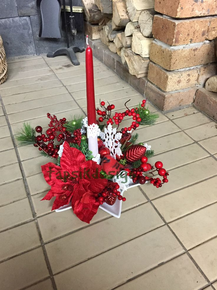 Christmas candle centerpiece. In colors red-white-green. Different kinds of christmas decorations, red bird, poinsettia, white wooden snowflakes.