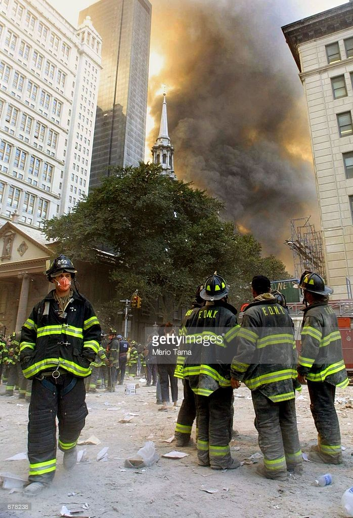 Firefighters watch as smoke rises from the site of the World Trade Center collapse September 11, 2001 in New York City after two hijacked airplanes crashed into the twin towers in a terrorist attack.