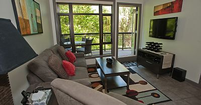 Playa del Sol 370 - Living Room with queen sized pull out and exit to the creekside balcony.  #kelowna #vacation #rental #vrbo #playadelsol370  www.playadelsol370.com