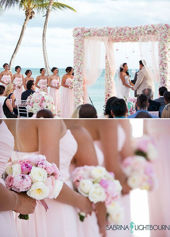 The couple exchanged personalized vows beneath a beautiful floral-covered arbor set against the backdrop of perfectly turquoise water.