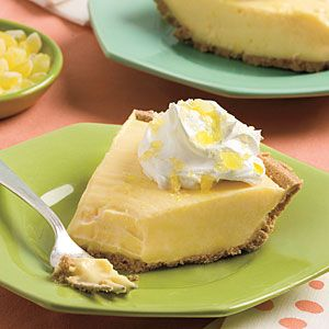 Frozen Lemonade Pie - 1 (12-oz.) can evaporated milk  2 (3.4-oz.) packages lemon instant pudding mix  1 tablespoon lemon zest  2 (8-oz.) packages cream cheese, softened $  1/2 teaspoon vanilla extract  1 (12-oz.) can frozen lemonade concentrate, thawed  1 (9-inch) ready-made graham cracker piecrust  Thawed frozen whipped topping.  Garnish: crushed lemon drop candies