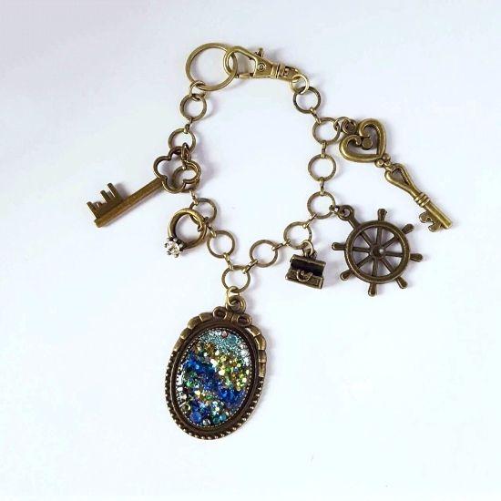 シンプルなバッグのアクセントに!アンティークゴールドにリボンの飾りがついたフレームの中に、深海の世界を表現しました。角度によって色を変える深い色のラメが輝きます。指輪、宝箱、宝箱の鍵チャームが合わさって、「深海へ宝物探し」という一つのストーリーになっている他にはないバッグチャームです。●カラー:アンティークゴールド(金古美)●サイズ:バッグチャーム金具の長さ:16㎝、フレームのサイズ:縦3.5㎝、横2.7㎝●素材:レジン、スワロフスキーストーン、グリッターラメ、バッグチャーム金具●注意事項:ラメは見る角度によって輝きが異なって見えます。強く引っ張ったり、ひっかけるとパーツが取れてしまう恐れがございますのでご注意ください。●作家名:パルティアアクセサリー/ 海の水/マーメイド/涼やか/小物/透明感と光沢/綺麗/クリア感/夏仕様/ツヤと輝き/ かわいい/ビーチ/マリンモチーフ/ファッション小物/透明感/ マリンパーツ/【配送】ゆうパック(保証・追跡サービスあり)レターパック(保証なし・追跡サービスあり)定形外郵便物…