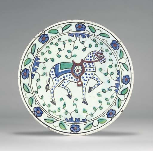 AN IZNIK POTTERY DISH OTTOMAN TURKEY, CIRCA 1640 With sloping rim on short foot, the white interior decorated in cobalt-blue, green and black underglaze and bole-red with a large figure of a trotting blue-spotted horse with bridle, four blue tufts issuing scrolling vine that fills the interstices, the rim with alternating green paired leaf and blue rosette motifs between black rings, the exterior with alternating blue and green motifs, 10 3/8in. (26.2cm.) diam.